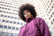 Afro Young Woman With Blank Expression Standing Against Built Structure