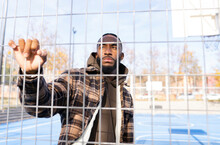 Thoughtful Young Man Looking Away Seen Through Fence In Sports Court On Sunny Day