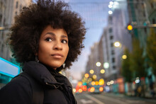 Afro Young Woman In Looking Away While Standing In City At Evening