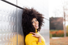 Curly Hair Woman Smiling While Leaning On Silver Wall