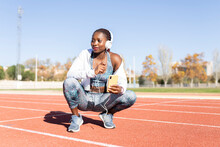 Female Sportsperson With Mobile Phone Listening Music While Crouching On Sports Track During Sunny Day