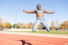 Excited Female Sportsperson Jumping With Arms Outstretched Over Running Track Against Clear Sky