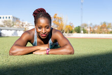Smiling Female Sportsperson Lying On Grass During Sunny Day