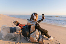 Mid Adult Woman Taking Selfie While Sitting With Dogs At Beach During Sunset