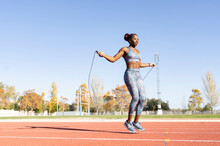 Female Sportsperson Skipping With Jump Rope Over Running Track On Sunny Day