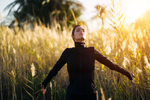 Young Woman With Eyes Closed Standing Against Plants During Sunset