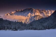 Scenic View Of Snowy Forest Against Mountains During Sunset