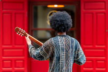 Young Man Playing Guitar While Standing In Front Of Building