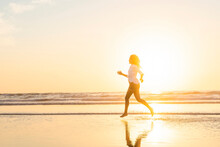 In Silhouette Of Woman Running In Sea During Sunset