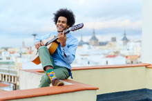Happy Young Man Playing Guitar While Sitting On Terrace Against Sky