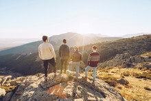 Friends Looking At View While Standing On Mountain During Sunny Day