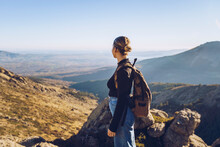 Female Hiker With Backpack Looking At View While Standing On Top Of Mountain