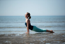 Mature Woman Practicing Upward Facing Dog Position At Beach Against Clear Sky