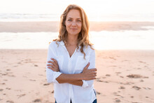 Smiling Woman Standing With Arms Crossed At Beach