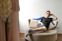 Confident Mid Adult Drag Queen Sitting On Couch Against White Wall