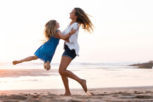 Mother Carrying Daughter While Playing At Beach