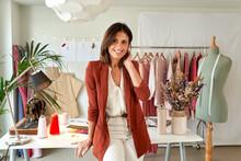 Confident Female Fashion Designer Leaning On Desk Against Clothes Rack At Atelier