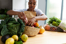 Woman With Apron In Kitchen , Unpacking Freshly Bought Organic Fruit And Vegetables