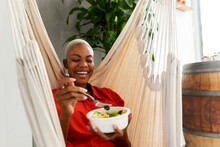 Woman Sitting In Hammock Eating Bowl Of Salad