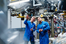 Mature Male Technicians In Overalls Examining Machine Part In Factory