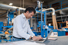 Portrait Of Carpenter Using Laptop In Production Hall