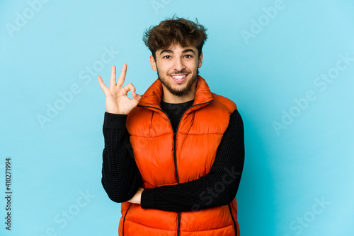 Tela Young arab man on blue background winks an eye and holds an okay gesture with hand
