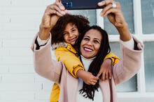 Girl Embracing Mother Taking Selfie With Smart Phone Against Wall