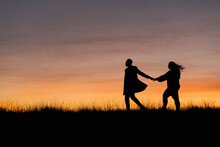 In Silhouette Of Man Holding Hand Of Woman While Walking Against Sky During Sunset