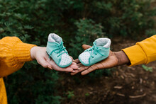 Close-up Of Couple Holding Baby Booties At Forest