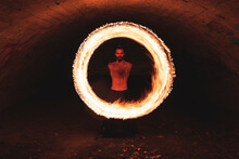 Hipster Male Performing Fire Ring In Tunnel