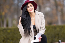 Smiling Beautiful Woman Wearing Hat While Sitting In Park During Weekend