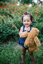 Cheerful Baby Girl Holding Teddy Bear Standing On Grassy Land Against Plants In Park