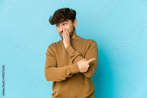 Vászonkép Young arab man on blue background saying a gossip, pointing to side reporting something