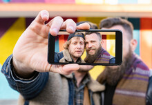 Close-up Of Gay Couple Taking Selfie With Mobile Phone