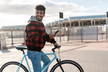 Smiling Man With Mobile Phone Looking Away While Standing On Bicycle During Sunny Day
