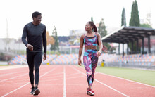 Male And Female Sportsperson Walking On Track Against Clear Sky