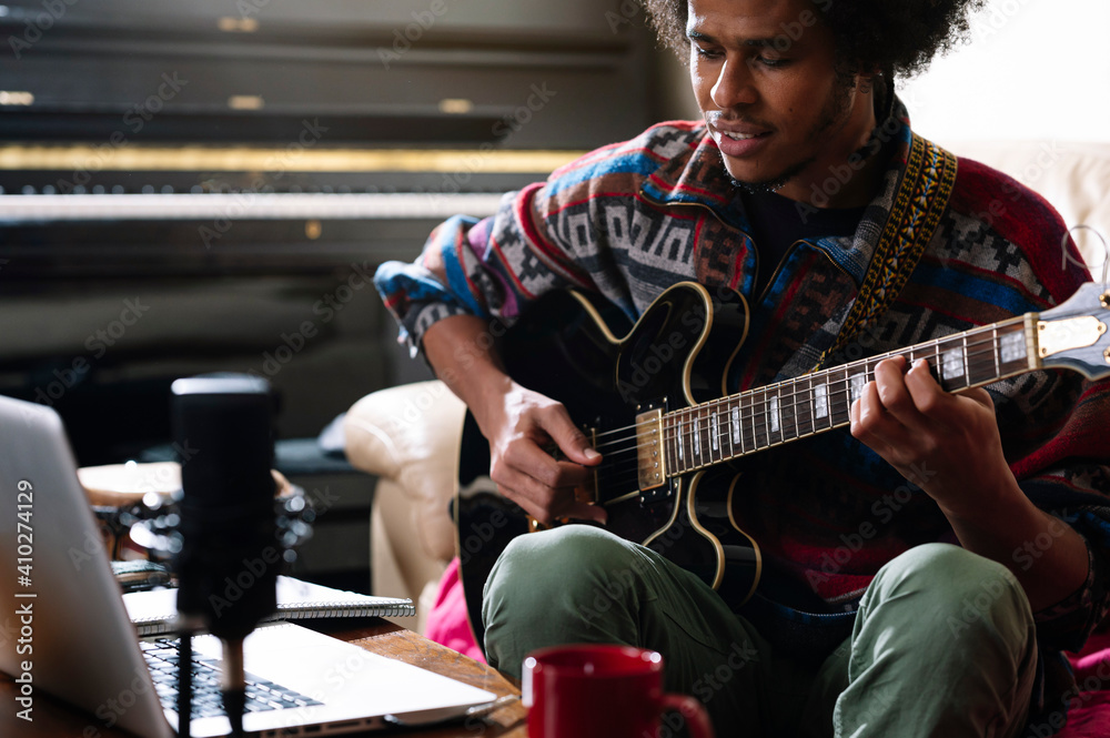 Afro young man learning to play guitar through laptop in living room