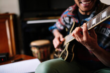 Smiling Male Musician Playing Guitar At In Living Room