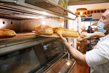 Male Chef In Protective Face Mask Removing Fresh Bread From Oven In Bakery Kitchen
