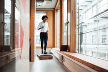 Active Young Businessman Jogging On Treadmill Against Window In Workplace