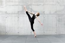 Dancer In Black Leotard Dancing In Front Of Concrete Wall