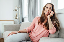 Mature Woman Talking On Phone Call While Sitting On Sofa At Home