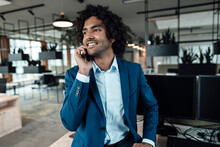 Smiling Young Businessman Talking On Smart Phone While Looking Away At Workplace