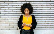 Beautiful Woman With Afro Hair Using Smart Phone While Standing Against Brick Wall