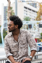 Stylish Mid Adult Man With Afro Hair Wearing Sunglasses While Sitting In City