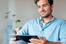 Man Using Digital Tablet While Sitting At Home