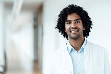 Smiling Young Male Doctor With Black Curly Hair At Hospital Corridor