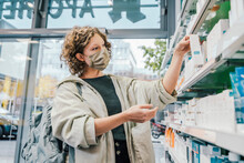 Female Customer Wearing Protective Face Mask While Checking Medicine In Chemist Shop