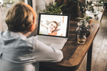 Mother Having Video Call With Smiling Daughter Through Video Call On Table At Home