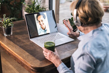 Grandmother Waving To Granddaughter On Video Call Through Laptop While Having Juice At Home